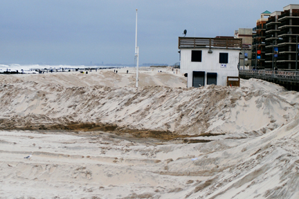 The sand berms that were suppose to protect the lifeguard shack and the ocean from reaching the streets.